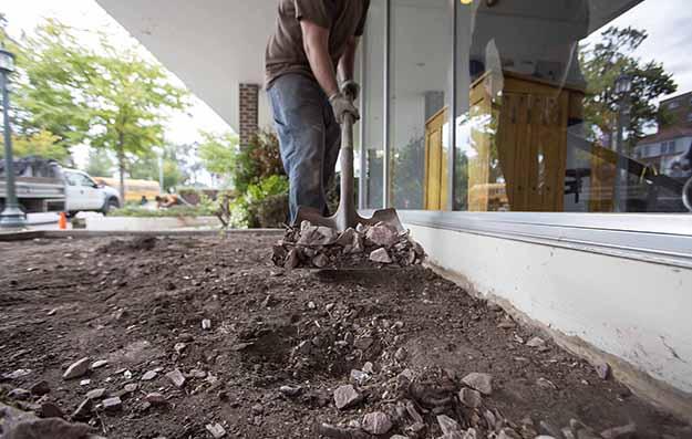 Shoveling rock and soil Landscape Crew Now Hiring